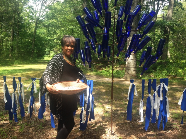 "The ""Bottle Tree"" was part of an experience that started with the performer explaining the origins of the tree and asking you to perform a task in exchange for a blessing. This is the artist with her piece."